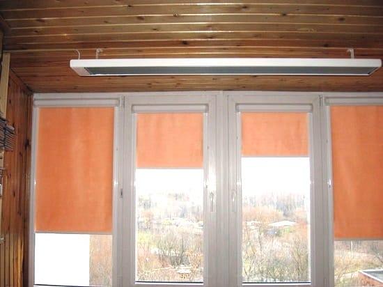 Инфракрасный обогреватель, закрепленный на потолке балкона