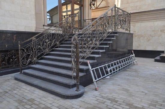 Лестница с элементами ковки и гранитными супенями