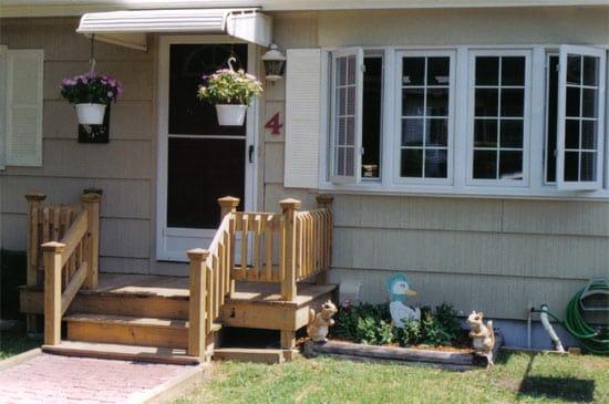 Крыльцо дома с деревянной лестницей