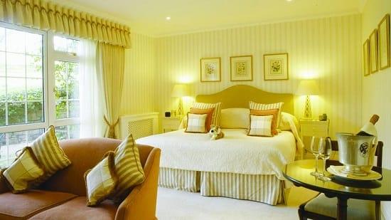 Желтые в полоску обои в классическом интерьере спальни