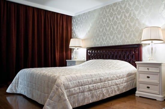 Серые с классическим рисунком обои в спальне