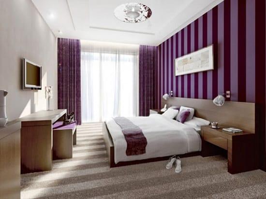 Фиолетовые обои в сочетании со светлой мебелью в спальне