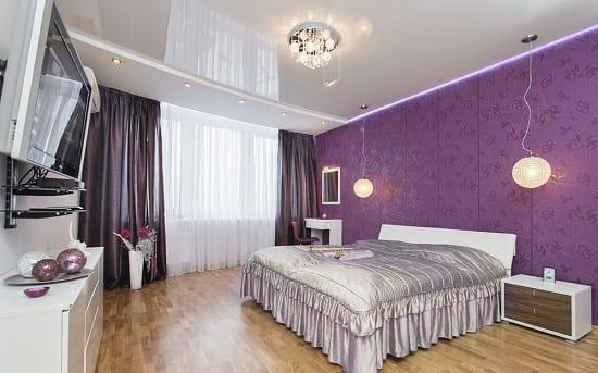 Установка глянцевого натяжного потолка серого цвета в сиреневой спальне