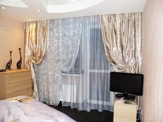Богатые бежевые шторы из атласа в интерьере спальни