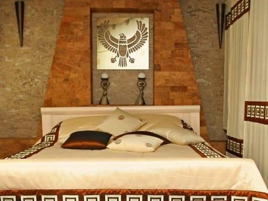 Национальный орнамент на текстиле и статуэтки в спальне египетского стиля