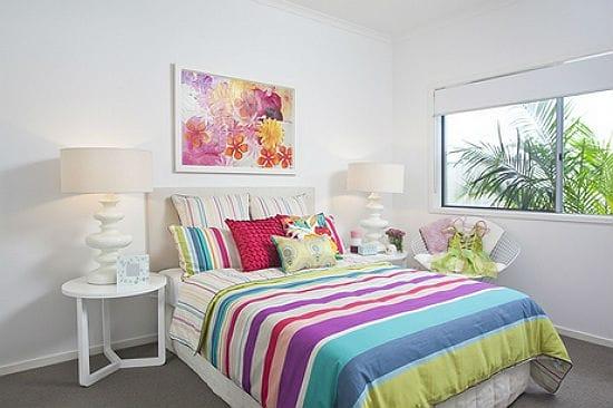 Яркий текстиль в белой спальне с простой однотонной отделкой