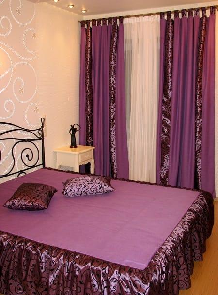 Яркий текстиль фиолетового цвета в спальне со светлой отделкой