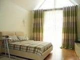 Полосатые шторы на окнах мансардной спальни