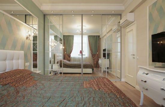 Встроенный шкаф с зеркальным фасадом в интерьере спальни