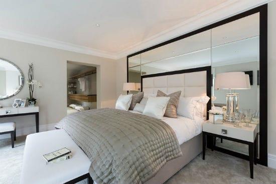 Красивое оформление стены спальни при помощи большого зеркала
