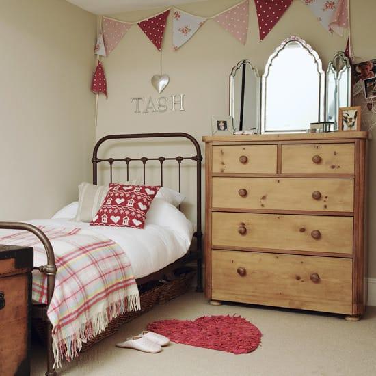 Деревянные комоды и металлическая кровать в спальне кантри для девочки