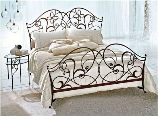 Красивая кровать с ажурной ковкой в спальне