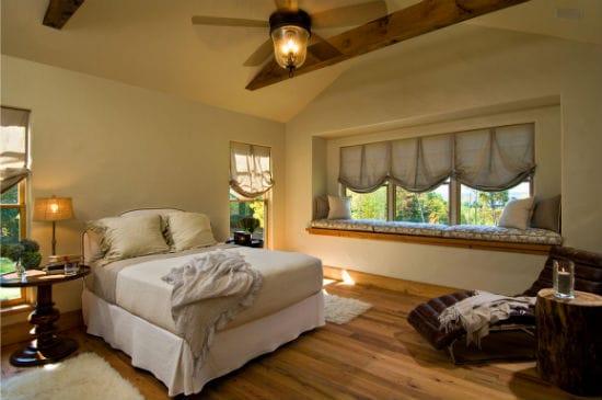 Красивое оформление окна спальни мягкими подушками и короткими занавесками