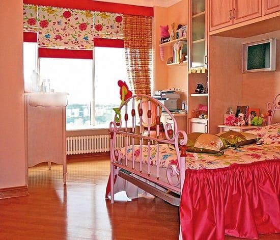 Практичные римские шторы яркой расцветки в оформлении спальни девочки