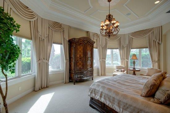 Красивые однотонные шторы в классическом стиле в дизайне бежевой спальни