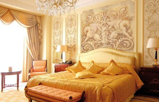 Классический интерьер спальни с красивой фреской на стене у кровати