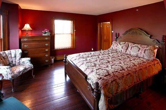 Бордовая спальня в английском стиле с массивной резной кроватью