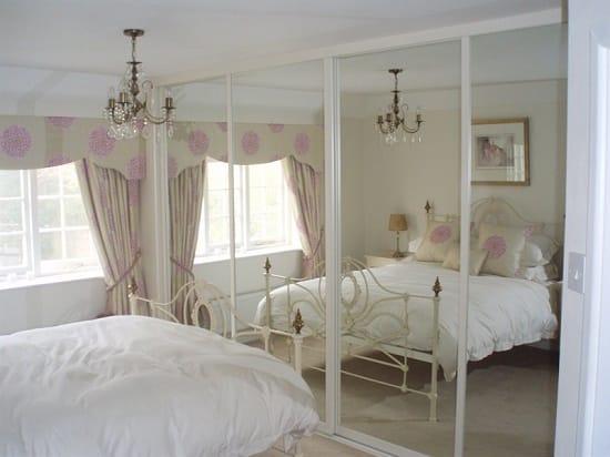 Установка шкафа с зеркальным фасадом в узкой спальне