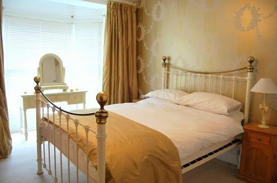 Небольшая золотистая спальня с металлической кроватью и трюмо