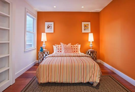 Использование контрастной бело-оранжевой отделки стен в дизайне спальни